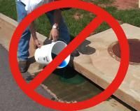 "Person dumping a blue chemical down a storm drain with a large red circle and diagonal ""Do Not"